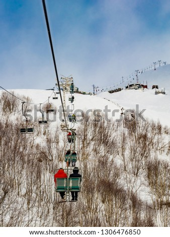 Extreme cable car ride. Winter holidays in the mountains. Snow-covered mountain slopes. Skiers and tourists. #1306476850