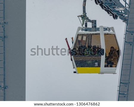 Extreme cable car ride. Winter holidays in the mountains. Snow-covered mountain slopes. Skiers and tourists. #1306476862