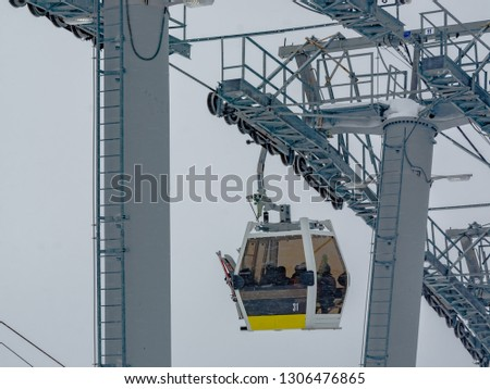 Extreme cable car ride. Winter holidays in the mountains. Snow-covered mountain slopes. Skiers and tourists. #1306476865