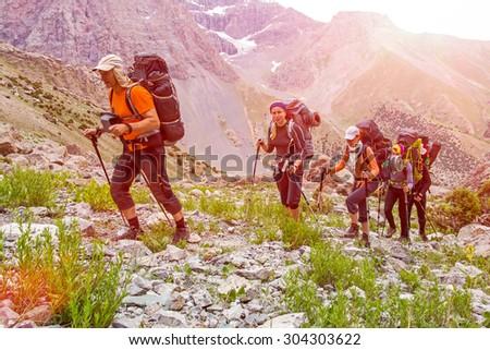 extreme climbers scrambling up. ...