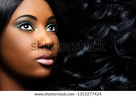 Extreme close up beauty portrait of beautiful young african woman with professional make up. Girl looking at corner with long curly hair next to face.