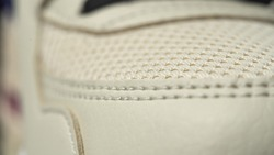 Extreme close up footage of perfect toe sneaker dolly in. Beige color.