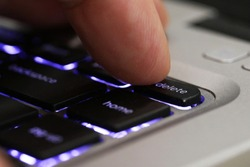 Extreme close up of a finger pressing the delete tab on a computer keyboard. Blue back lit computer laptop keys with a digit pushing the delete button. Cancel culture concept