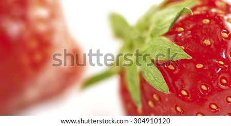 extreme close up of a strawberry. one other strawberry unsharp in the background