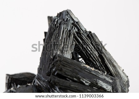 Extreme close up of black tourmaline mineral isolated over white background in focus stacking technique