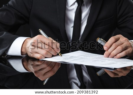 Extreme close up of female business hand signing document.