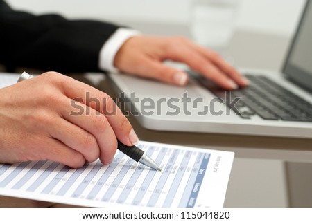 Extreme close up of female business hands working on accounting document.