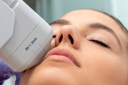 Extreme close up of HIFU treatment on female face. Therapist doing cosmetic plasma lift with high intensity focal ultrasound device.