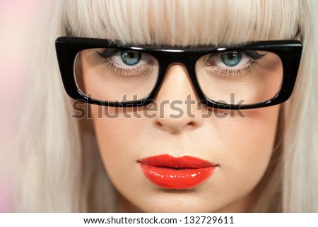 extreme close up of woman with retro black plastic glasses.