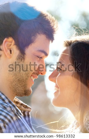 Extreme Close up portrait of romantic couple looking at each other outdoors.