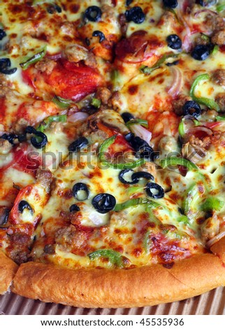 """Extreme close-up view of a section of a pizza """"supreme"""" with all the trimmings"""