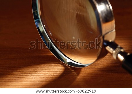 Extreme closeup of magnifying glass standing on wooden surface with beam of light