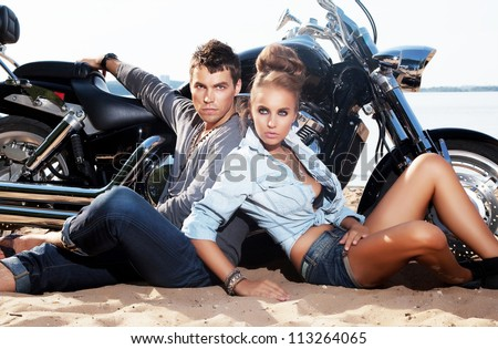 Extreme couple sitting by motorcycle on the beach. Adventure and travel concept - stock photo
