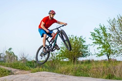 Extreme cycling concept, cyclist jumping on a mountain bike. Cyclist in a bright orange t-shirt and helmet.