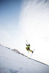extreme freestyle ski jump with young man at winter season on the background of blue sky . snowkiting.