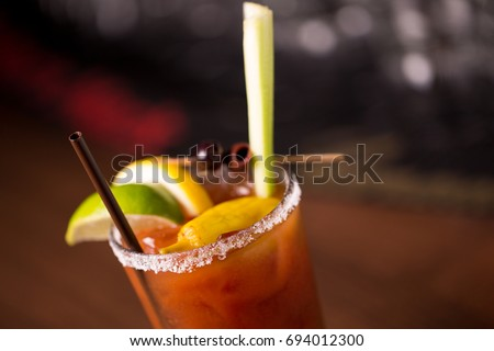 Extreme macro close up of vodka tomato juice bloody mary mix cocktail in salted rim tumbler garnished by lemon lime with olive and celery stalk on retro diner bar with blurry restaurant background