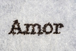 Extreme macro shot of the word 'Amor' typed with on white paper. Grungy textured mood. Love in french