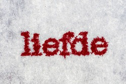 Extreme macro shot of the word 'liefde' typed on white paper. Grungy textured bloody mood. Liefde in dutch.