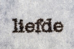 Extreme macro shot of the word 'liefde' typed with on white paper. Grungy textured mood. Liefde in dutch.