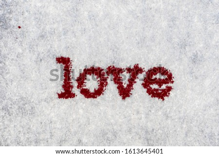 Extreme macro shot of the word LOVE typed on white paper. Grungy textured bloody mood.