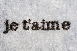 Extreme macro shot of the words je t'aime typed on white paper. Grungy textured bloody mood.. French text.