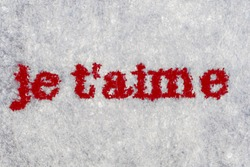 Extreme macro shot of the words je t'aime typed on white paper. Grungy textured bloody mood. French text.