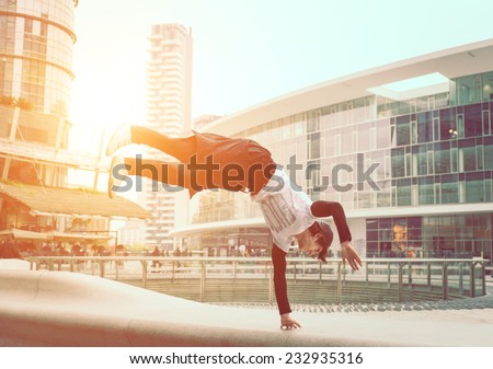extreme parkour in business center. young boy performing some jumps from parkour discipline