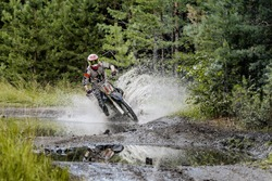 extreme racing motorcycles on forest. splashes water and mud from puddles. competitions on Enduro