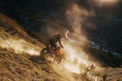 Extreme Rider climbing sand mountain top on off-road cross enduro motorcycle. Beautiful mountains landscape down on background, colourful autumn forest and river in sunshine