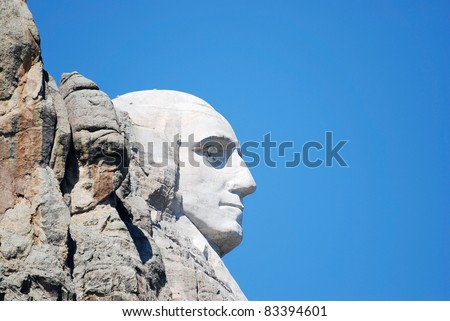 Extreme side view of Mount Rushmore showing only the head of George Washington ... white against bright blue sky.
