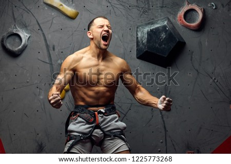 Extreme sports or hobby concept- athletic climber with naked torso screaming on peak of overwhelming emotions, celebrating triumph.