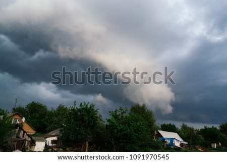 Extreme thunderstorm shelf cloud. Summer landscape of severe weather.