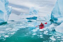 extreme tourism, winter kayaking in Antarctica, adventurous man paddling on sea kayak between icebergs