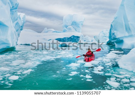 extreme tourism, winter kayaking in Antarctica, adventurous man paddling on sea kayak between icebergs