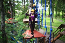 extreme vacation, girl in a yellow helmet rope park active holidays in the forest