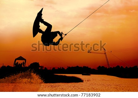 extreme wakeboarding surfer surfing on water with beautiful sky background