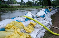 Extreme weather - a line of sand bags and hoses to pump water out of flooded basements in Düsseldorf, Germany