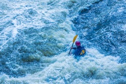 Extreme whitewater rafting trip. A one person in kayak practise traversing the water rapids. Kayaker paddling on the mountain river. Kayaking concept. Artificial noise, selective focus, backlight