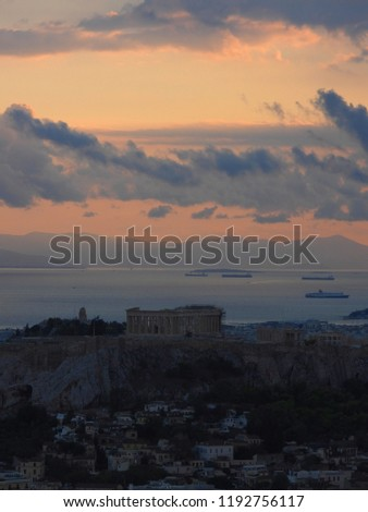 Extreme zoom dramatic photo of iconic Acropolis hill and the Parthenon as seen from Lycabettus hill at sunset with heavy dark clouds Stock photo ©