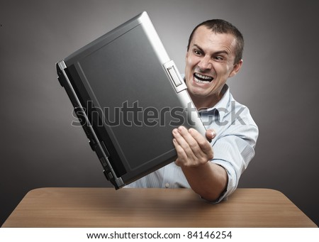 Extremely angry businessman smashing his laptop on the desk