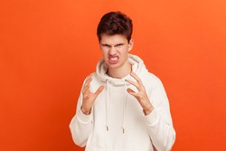 Extremely angry frustrated teenager in casual style sweatshirt with hood dissatisfied with service, scary grin on his face. Indoor studio shot isolated on orange background