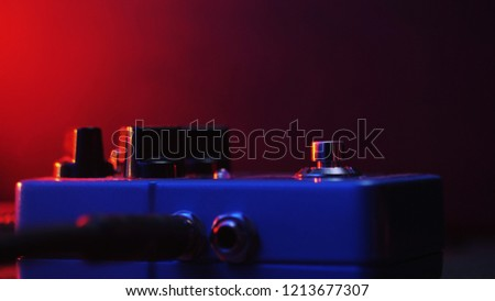 Extremely close up of button for effect electro guitar pedal. Red neon light in night club during show concert. #1213677307