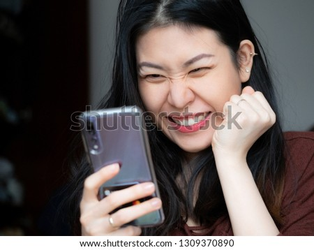 Extremely excited young Asian beautiful woman amazed by mobile app sale message looking at smartphone, euphoric girl winner holding, looking cell mobile phone screaming with joy. Big eyes