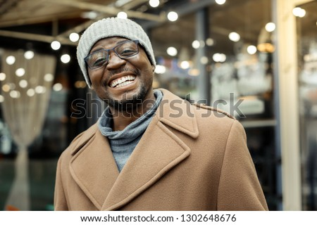 Extremely happy. African-American man wearing hat feeling extremely happy after seeing his wife #1302648676