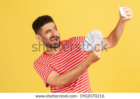 Extremely happy satisfied man blogger in striped t-shirt making selfie photo with bunch of dollars on smartphone and winking, bragging with wealth. Indoor studio shot isolated on yellow background Сток-фото ©