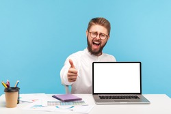 Extremely happy satisfied man office manager showing thumbs up sitting at workplace with empty screen laptop, satisfied with new pc, advertising area. Indoor studio shot isolated on blue background