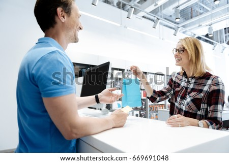 Extremely happy young lady making purchases at electronics store
