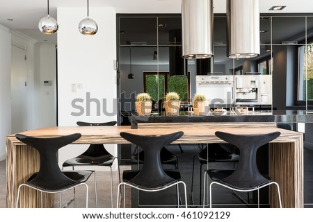 Extremely modern kitchen and dining room arranged with metal and glass materials