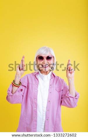 Extremely positive. Cheerful lady wearing pink jacket and sunglasses feeling extremely positive #1333272602