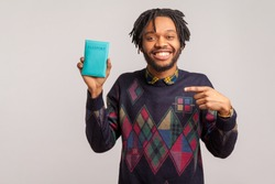Extremely satisfied african man with dreadlocks pointing finger on passport in his hand with toothy smile on face, happy with travel abroad. Indoor studio shot isolated on gray background